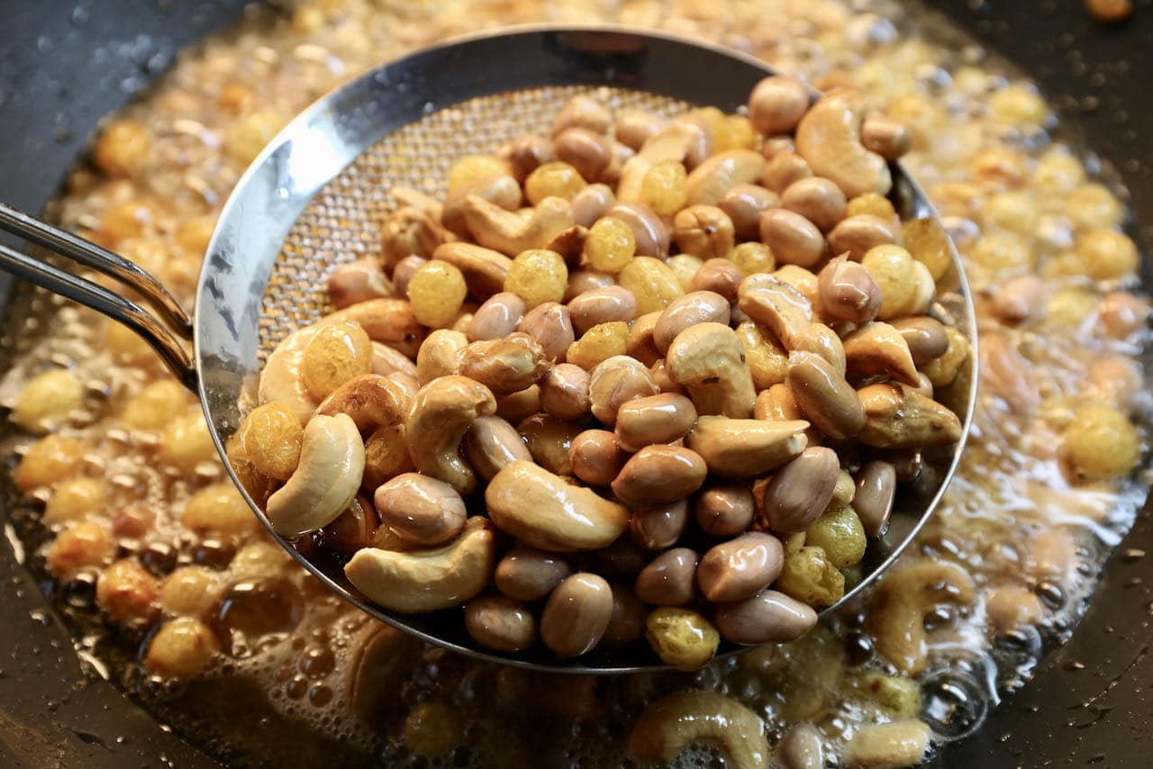 After frying the moong dal add raisins, cashews and peanuts to the hot oil.