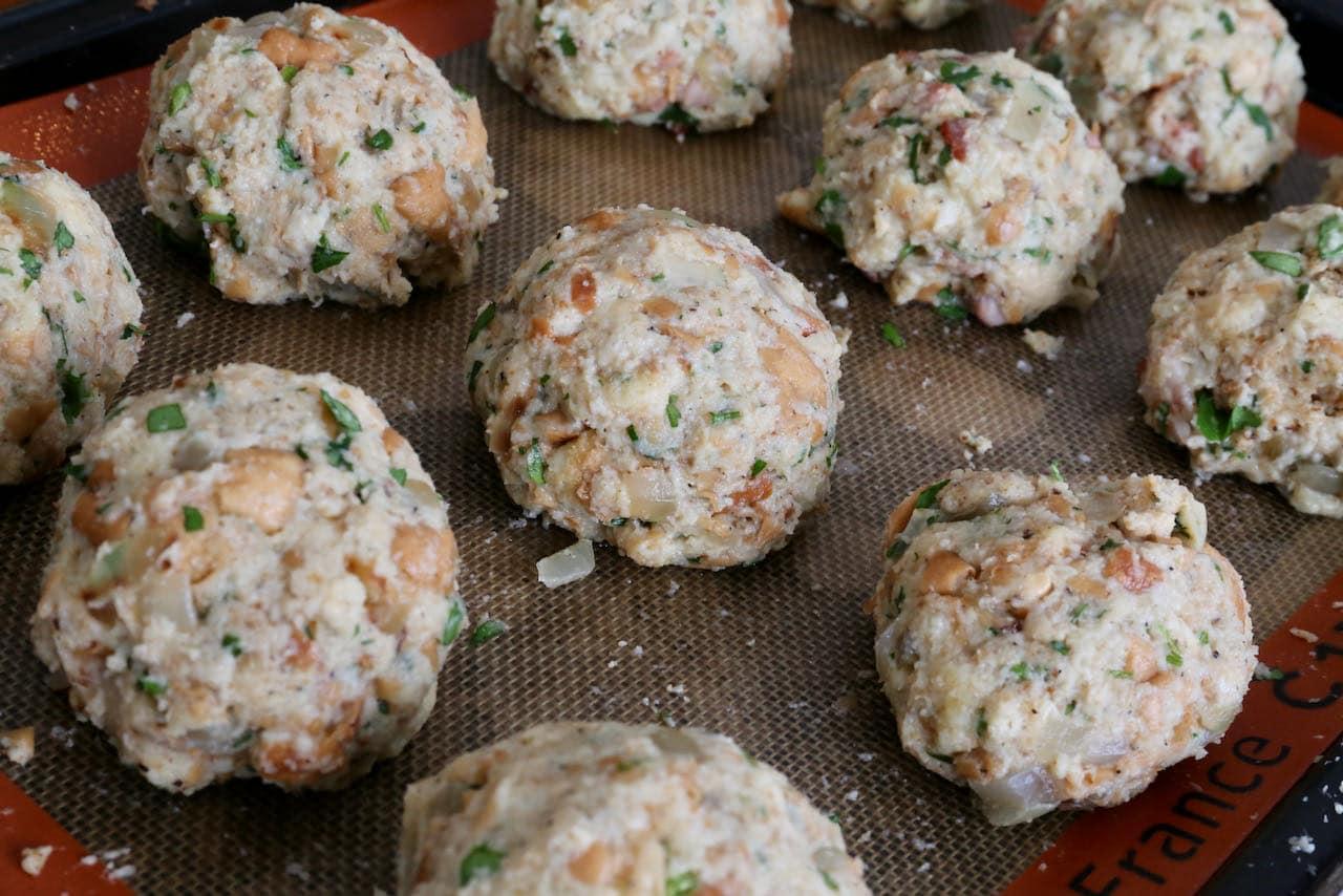 Let Semmelknödel German Bread Dumplings rest on a baking sheet before boiling.