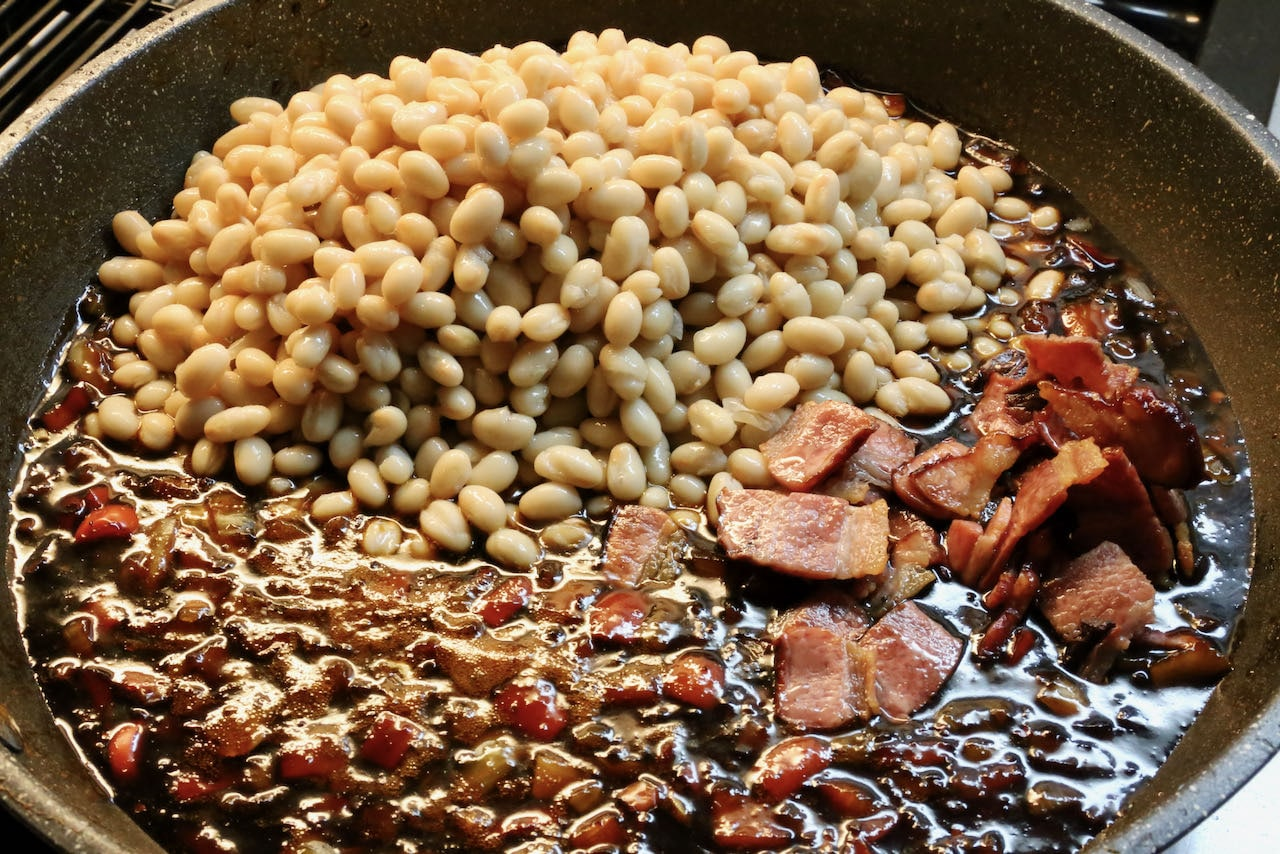 Add canned navy beans and crispy bacon to the smoky sauce.