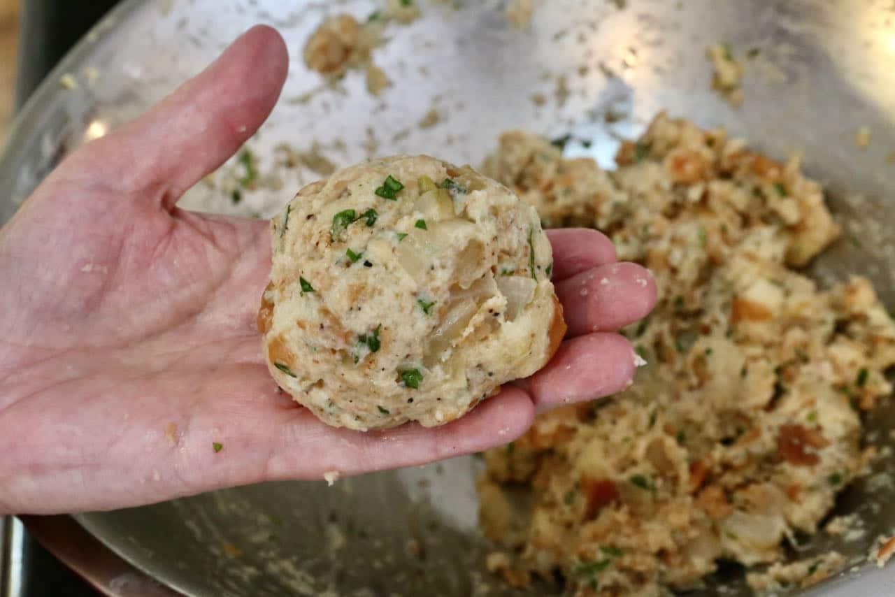 Use wet hands to form large Speckknödel bread dumpling balls.