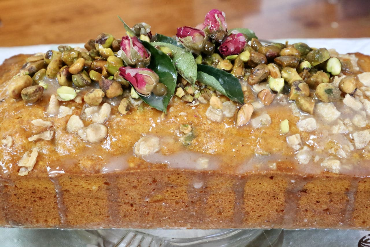 Pour cardamom glaze over the curry leaf, rose buds and pistachio to help attach them to the top of the cake.