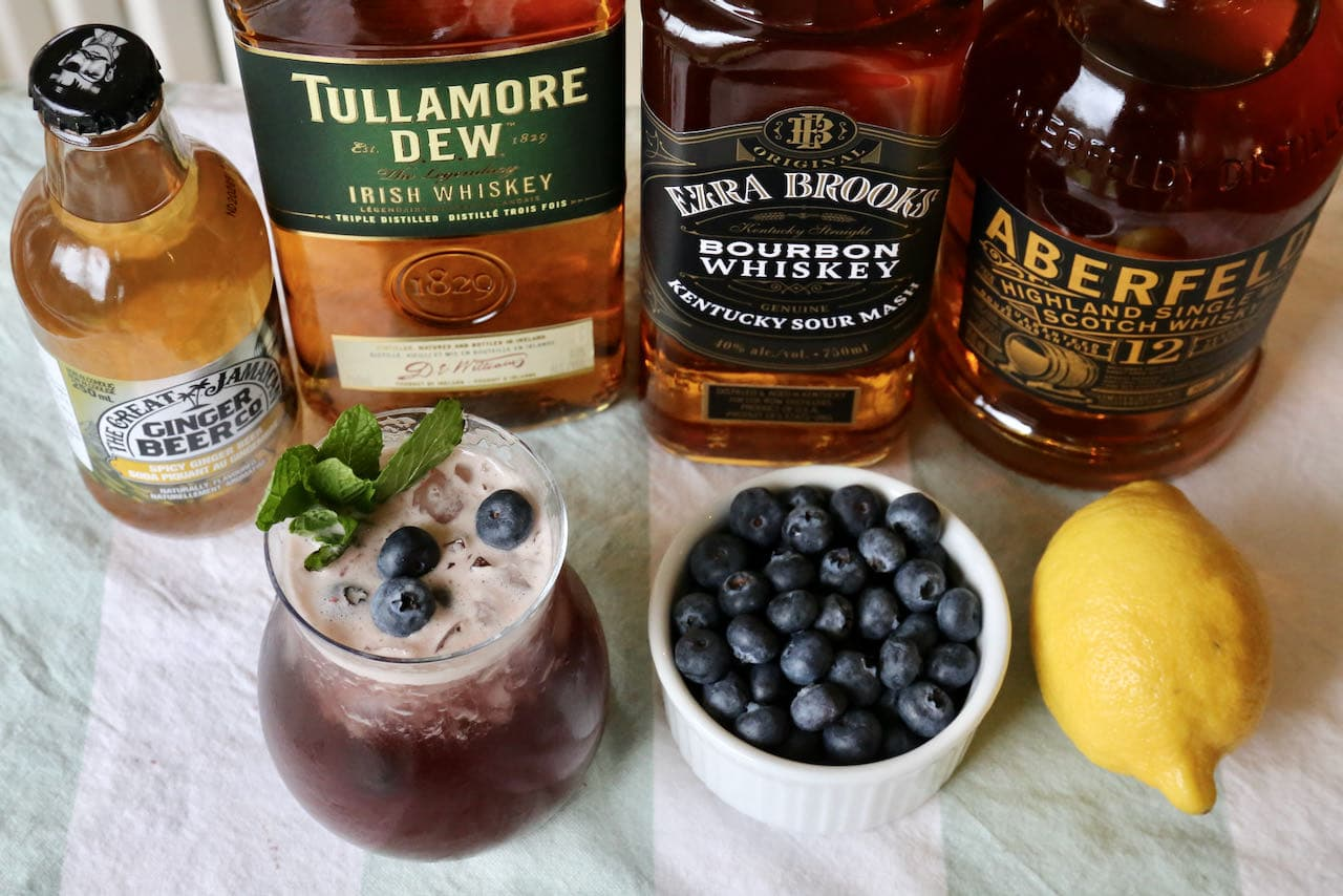 Our Blueberry Buck cocktail is garnished with a mint sprig and fresh blueberries.