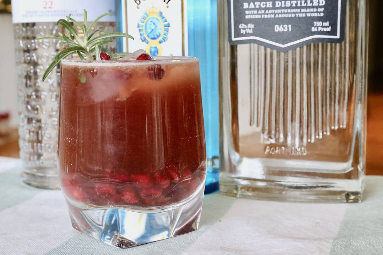 Our Pomegranate Gin Fizz recipe is garnished with pomegranate seeds and rosemary sprig.