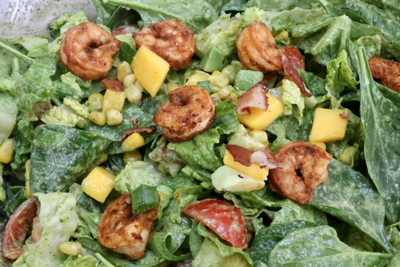 Toss salad in dressing then top with Cajun shrimp, crispy bacon and mango chunks.