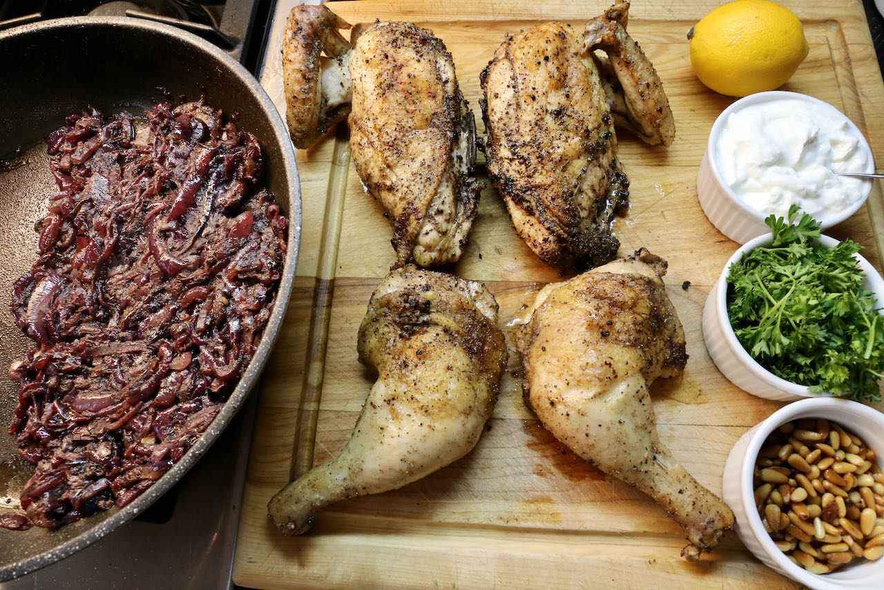 Assemble Musakhan with roasted chicken, caramelized onions, pine nuts, parsley, lemon and yogurt.