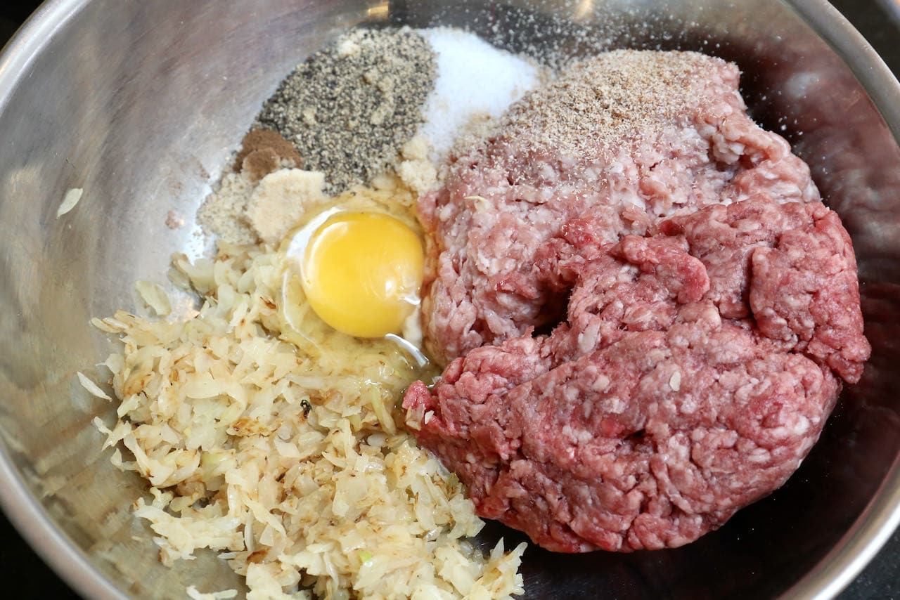 In a large bowl mix ground meat, onions, egg and spices.