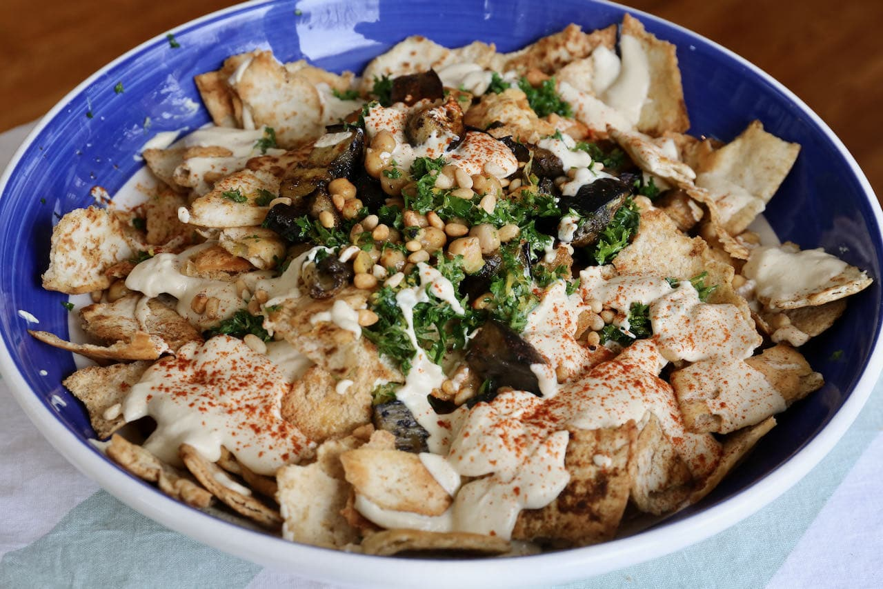Serve Eggplant Fatteh immediately as the crunchy pita pieces get soft and soggy quickly.