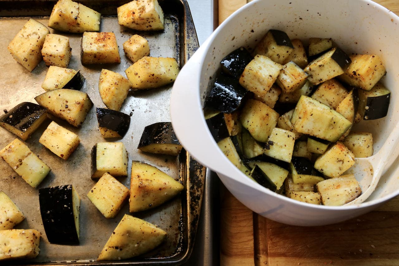 Begin preparing Lebanese Fatteh by tossing eggplant cubes in oil and spices and roasting in the oven on a baking sheet.