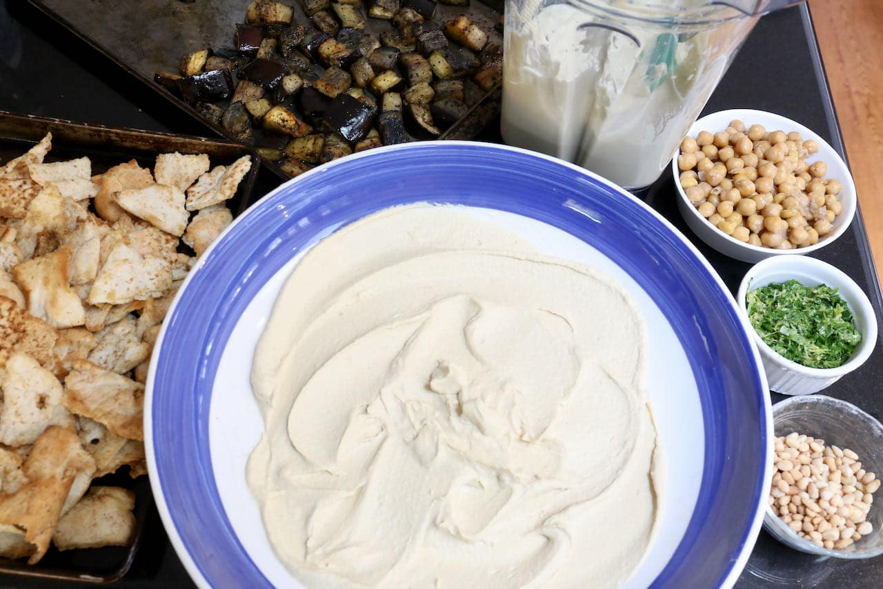 Eggplant Fatteh Assembly: Layer hummus, baked pita, roasted eggplant, cooked chickpeas, parsley and pine nuts.