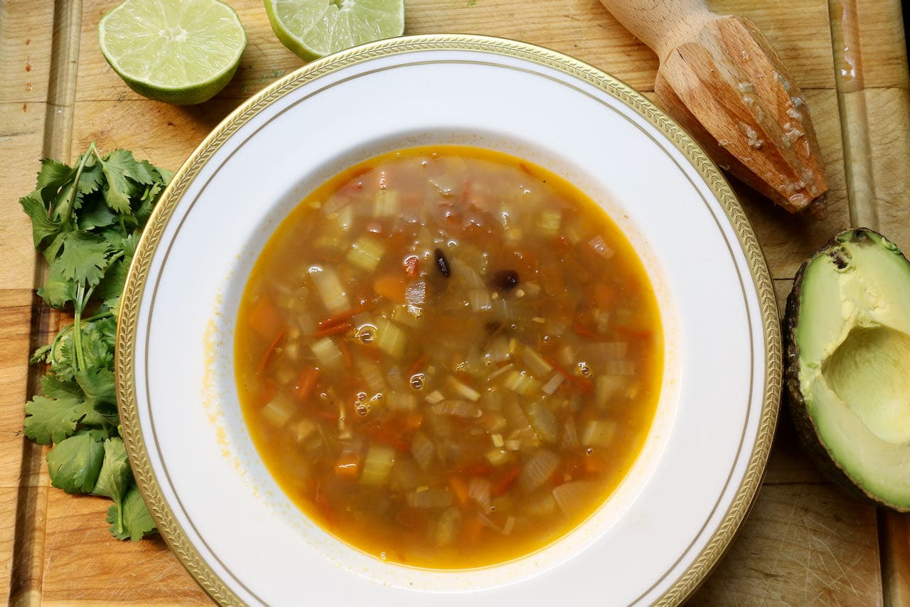 Assemble Mexican bean soup by topping with sour cream, avocado, cilantro and lime.
