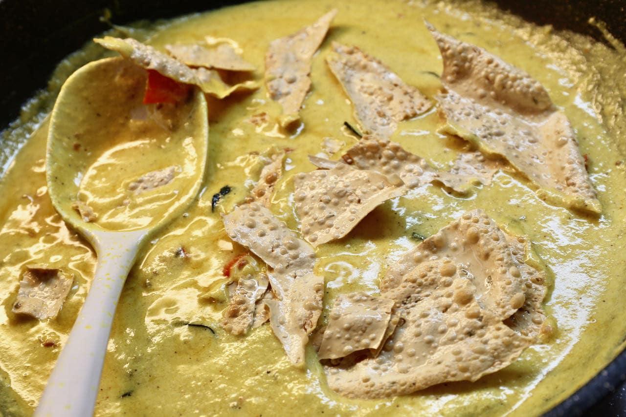 Toss Papad Ki Subji turmeric curry sauce with pieces of crunchy poppadom.