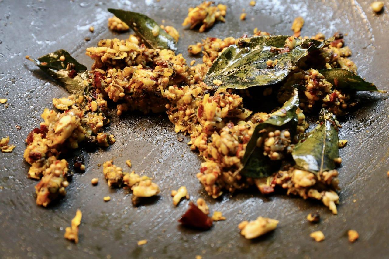 Fry Milagu Rasam garlic spice mixture with fresh curry leaf.