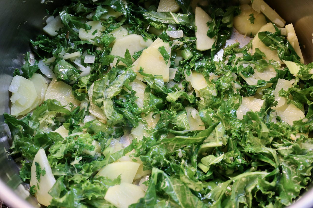 Saute oil with garlic, onion, sliced potatoes and chopped kale.