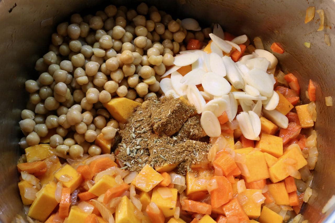 Cook chickpeas, garlic, carrots and squash with spices in a large pot.