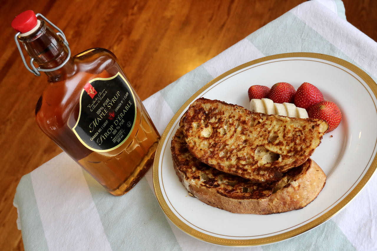 Serve Sourdough French Toast with maple syrup, banana slices and strawberries.