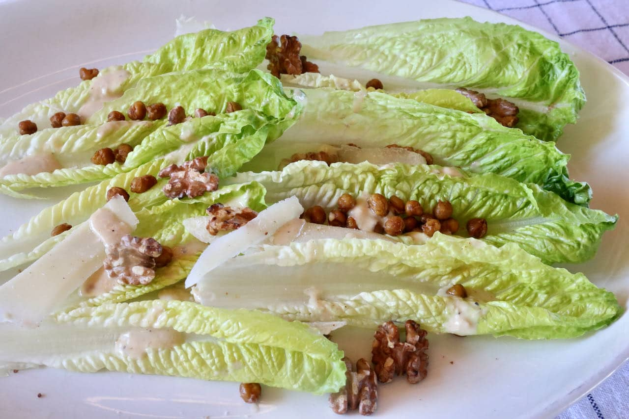 Our Romaine Salad with Tahini Caesar Dressing is topped with shaved parmesan cheese, roasted walnuts and crispy spiced chickpeas.