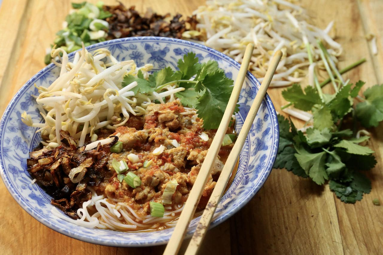 Serve Thai Pork Rib Soup topped with scallions, fried shallots, cilantro and bean sprouts.