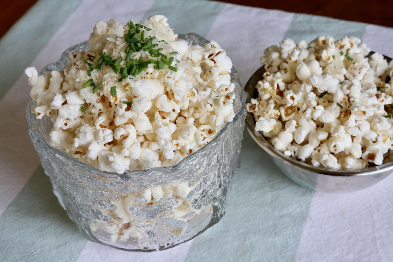 Indulge in gourmet Air Fryer Popcorn by tossing in melted butter, parmesan cheese, pepper and chives.