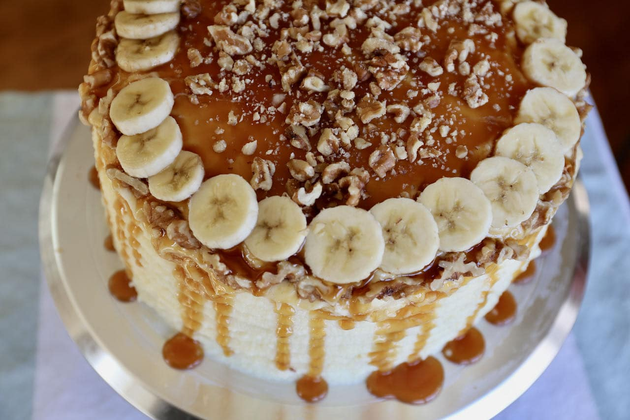 The Banoffee Cake is topped with sliced bananas, chopped walnuts and caramel drizzle.