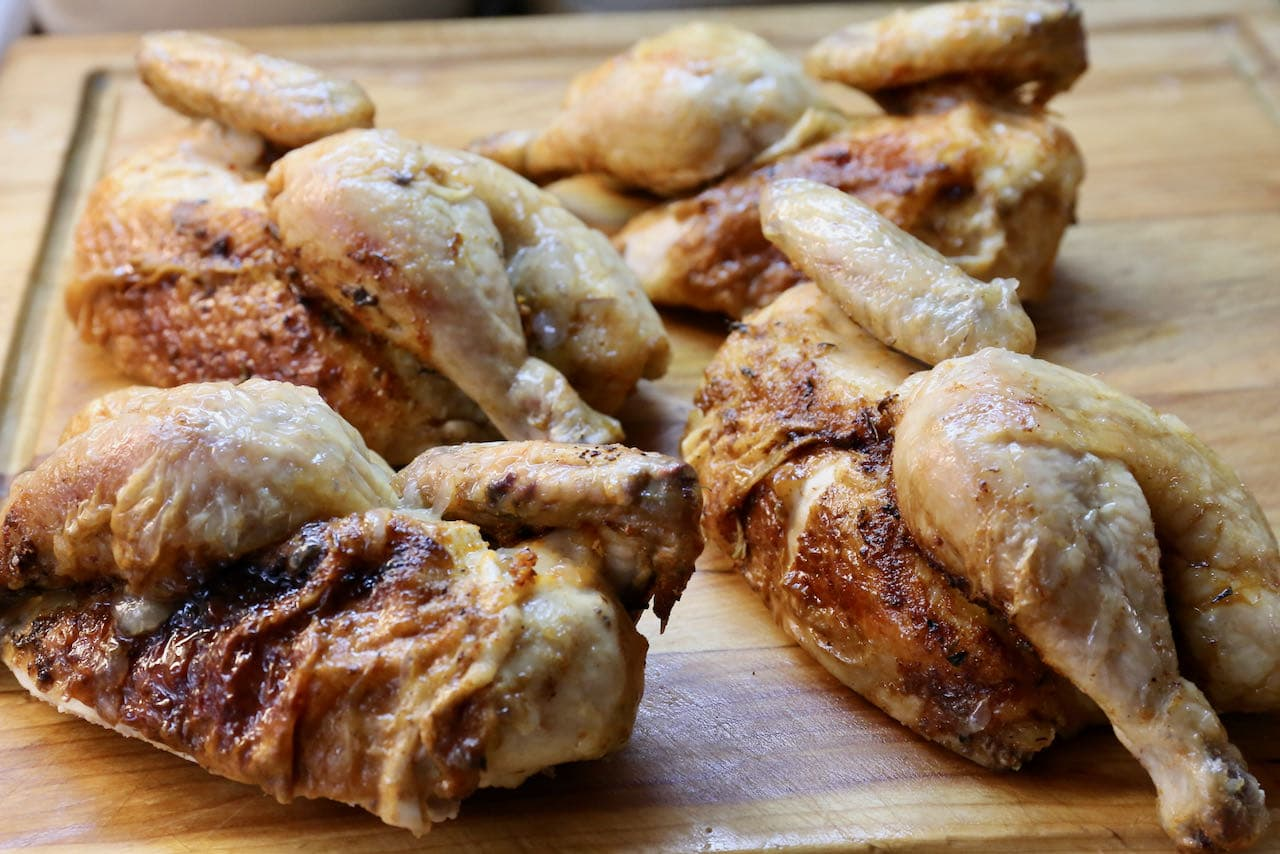 Divide Air Fried Cornish Hen into quarters using a sharp French knife on a cutting board.