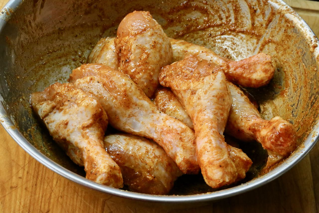 In a large mixing bowl toss chicken drumsticks in olive oil and spices.