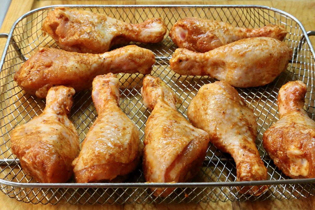Place seasoned chicken drumsticks in an air fryer basket.