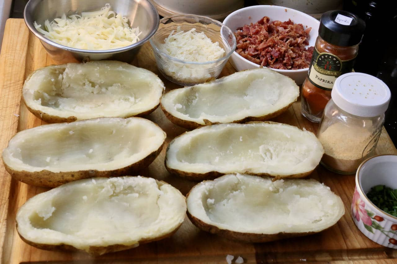 After baking the potatoes slice them in half and remove the centre so you can fill them with cheese, bacon and spices.