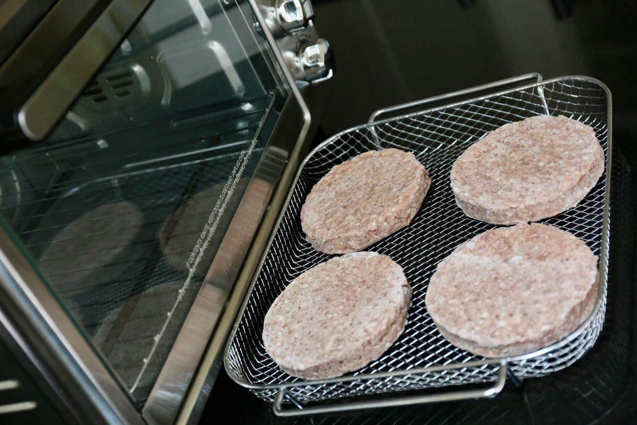 Cook frozen burger patties in an air fryer basket.