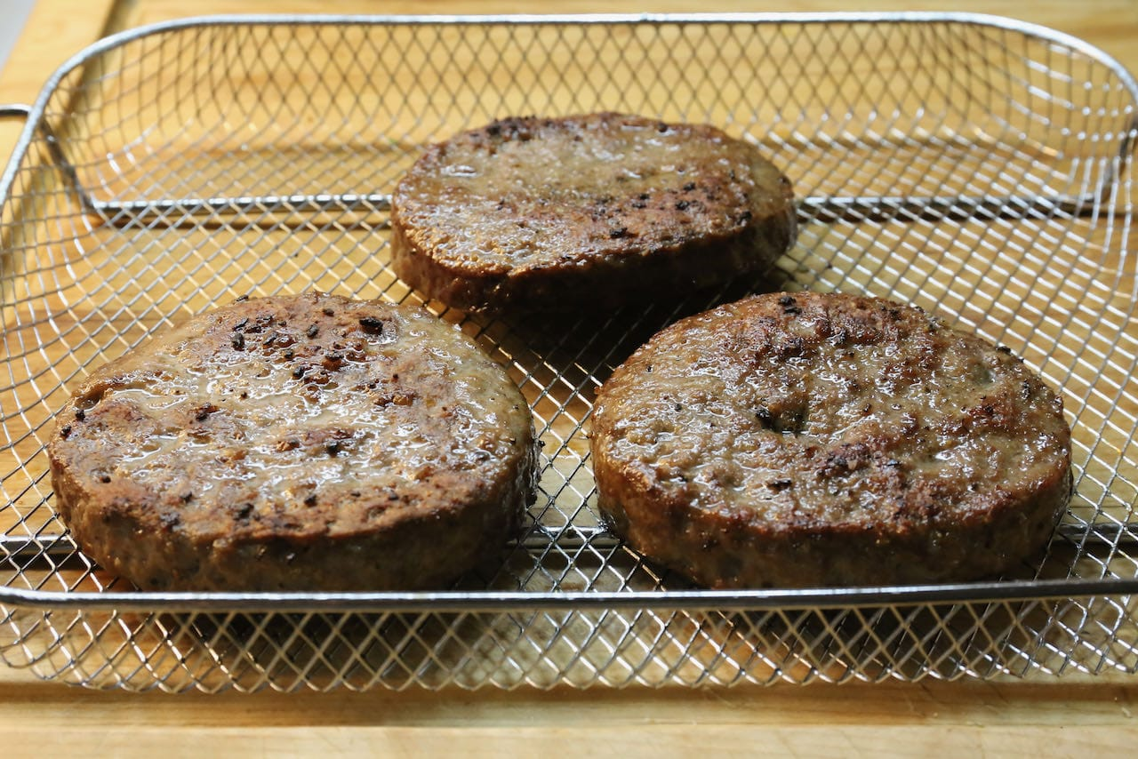 Remove frozen burger patties from your air fryer once they are browned and cooked through, approximately 15-20 minutes.