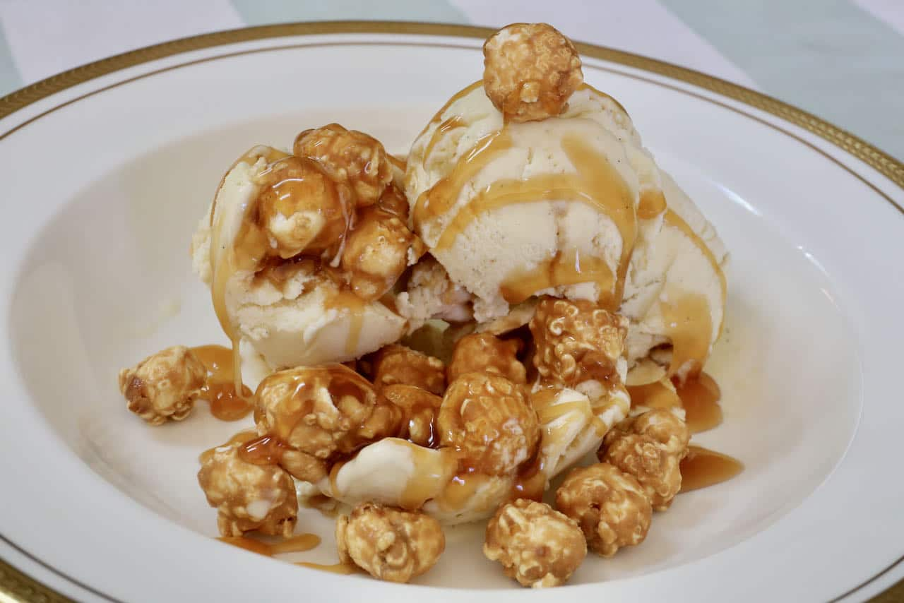Serve popcorn ice cream topped with caramel popcorn and caramel drizzle.