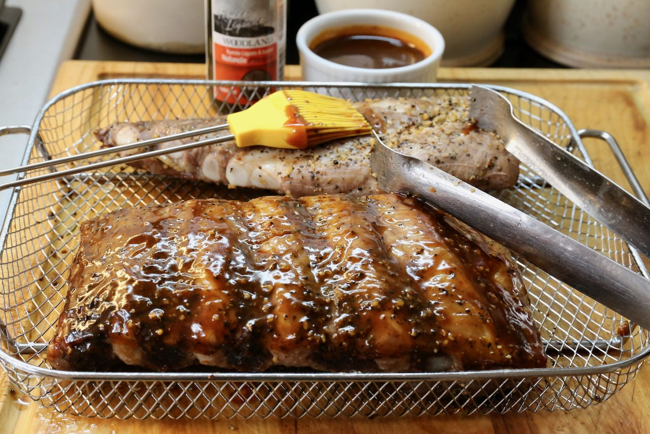 Use a pastry brush to slather Air Fryer Pork Ribs with your favourite barbecue sauce.
