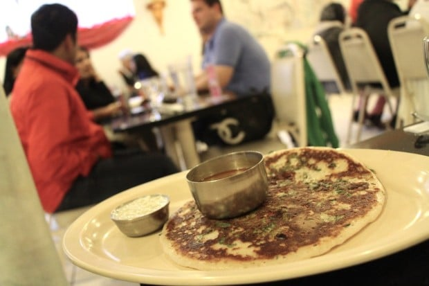 Uthapam Indian pancake dotted with tomato and peas.